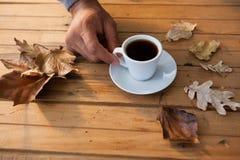 供以人员食用一个杯子与秋叶的无奶咖啡在木桌上 免版税库存照片