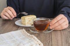 供以人员食用一杯茶与蛋糕的 库存图片