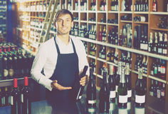 供以人员饮用卖主佩带的制服瓶酒 库存图片