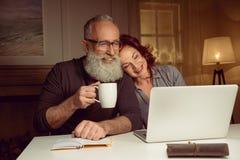 供以人员饮用的茶和使用膝上型计算机与妻子一起 库存照片