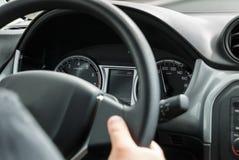供以人员驾驶一辆汽车用他的在方向盘的手 库存照片