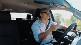 供以人员驾驶汽车和冲浪在手机 影视素材