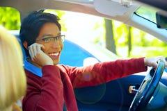 供以人员驾驶汽车和发表演讲关于手机 免版税库存图片