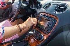 供以人员驾驶汽车和转动在仪表板的开关 免版税库存照片