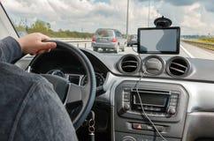 供以人员驾驶汽车用在方向盘的手和使用GPS航海 库存照片