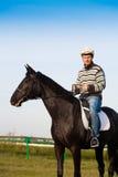 供以人员骑乘马,镶边套头衫,蓝色牛仔裤,帽子,关闭  库存图片
