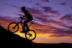 供以人员骑小山剪影的一辆自行车在日落 免版税库存图片