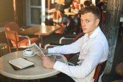 供以人员读在街道咖啡馆的一张报纸在看照相机的午餐 免版税库存图片