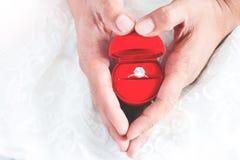 供以人员给定婚戒指他的有手心脏形状的女朋友 我快活 免版税库存图片