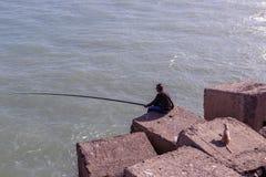 供以人员从岩石的渔在防波堤,猫watche边缘 库存照片