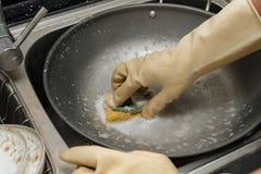 供以人员洗涤在厨房水槽的手一个平底锅与海绵 库存图片