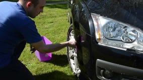 供以人员洗涤他有肥皂和海绵的喜爱的车轮在草坪 图库摄影
