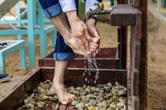 供以人员洗他的在沙子海滩的脚 免版税库存照片