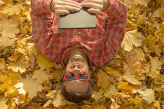 供以人员说谎在用黄色叶子报道的地面上和使用数字式片剂设备 库存照片
