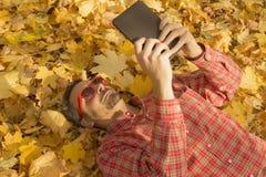 供以人员说谎在用黄色叶子报道的地面上和使用数字式片剂设备 库存图片