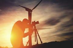 供以人员geodesist使用措施距离的经纬仪新的大厦的建筑的,当站立反对风轮机时 免版税库存图片