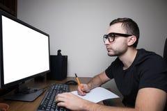 供以人员woking在白色屏幕显示器的个人计算机并且做通知 免版税库存图片