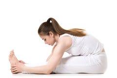 供以座位的向前弯瑜伽姿势 免版税库存照片