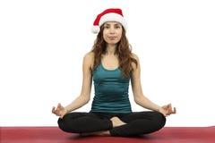 供以座位的姿势的年轻圣诞节妇女在瑜伽 库存图片