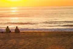 供以座位的日出两亚洲男性海滩 免版税库存图片
