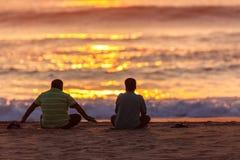 供以座位的日出两亚洲男性海滩 免版税图库摄影