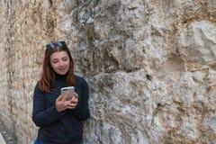 依靠古老中世纪街道石砖墙的女孩  红头发人键入的智能手机 使用手机检查的年轻女人 免版税图库摄影
