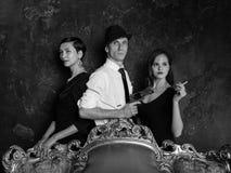 侦探故事射击在演播室 人二妇女 007座席 一个帽子的一个人有一把手枪和两名妇女的黑色的 免版税库存照片