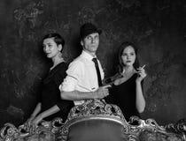侦探故事射击在演播室 人二妇女 007座席 一个帽子的一个人有一把手枪和两名妇女的黑色的 免版税库存图片