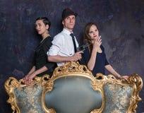 侦探故事演播室射击 人二妇女 007座席 一个帽子的一个人有一把手枪和两名妇女的黑色的 库存照片