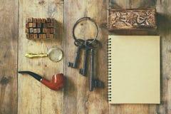 侦探概念 私家侦探工具:放大器玻璃,老钥匙,烟斗,笔记本 顶视图 葡萄酒被过滤的图象 库存照片