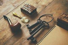 侦探概念 私家侦探工具:放大器玻璃,老钥匙,烟斗,笔记本 顶视图 葡萄酒被过滤的图象 免版税库存图片
