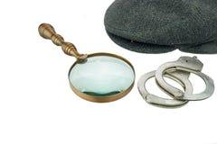 侦探温暖的盖帽、减速火箭的放大镜和真正的手铐 库存照片