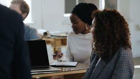 侧视图两女性公司同事,非洲和白种人专业经理在现代办公室队会议上 股票视频