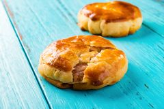 侧视图两甜微型耐嚼的蛋糕或chickee在蓝色木头结块 免版税库存图片