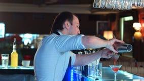 侧视图侍酒者倾吐的混杂的利口酒到准备的玻璃里通过鸡尾酒过滤器和谈话与客户 免版税库存图片