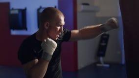 侧视图制定出在一个吊袋,慢动作的拳击手人打击 股票录像