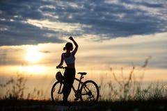 侧视图在自行车附近的招标女孩用向上放松在路的被举的手反对与云彩和坐的太阳的天空 免版税库存照片