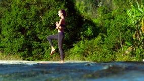 侧视图女孩在瑜伽在小河bankn的姿势树站立 股票录像