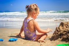 侧视图小女孩并且使用坐沙子海滨 库存照片