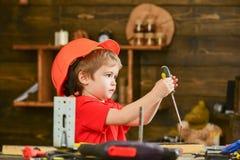 侧视图小孩约束螺丝到木板里 使用与螺丝刀的被集中的男孩 小的建造者 库存照片