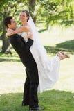 侧视图新郎举的新娘在庭院里 免版税库存图片