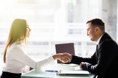 侧视图男人和妇女伙伴震动移交桌,维护的目光接触,确信的企业家准备好effec 库存照片