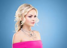 侧视图美丽白肤金发在桃红色礼服佩带的项链与 免版税图库摄影