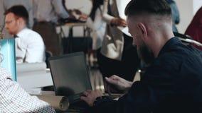 侧视图英俊的中部变老了欧洲上司商人与膝上型计算机一起使用在繁忙的现代办公室,人们走动 股票录像