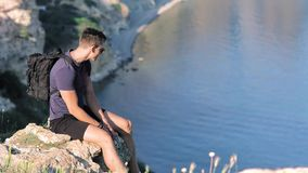 侧视图英俊的欧洲年轻男性旅客坐峭壁在干净的池塘中等轻率冒险附近 影视素材