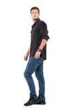 侧视图年轻偶然人走的回顾在肩膀 免版税图库摄影
