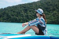 侧视图 单独坐船首和看风景的亚洲妇女 免版税库存图片