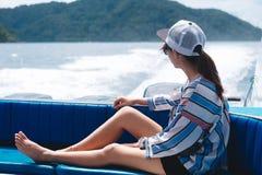 侧视图 坐亚洲的妇女支持小船和看scener 库存图片