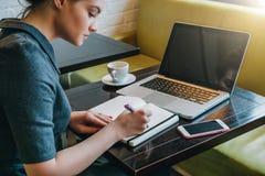 侧视图 坐在咖啡馆的桌上的年轻女实业家在前面 库存图片