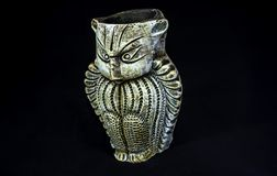 侧角观点的赤土陶器猫头鹰 做在与选择聚焦和被隔绝的黑背景的黏土外面 免版税库存图片